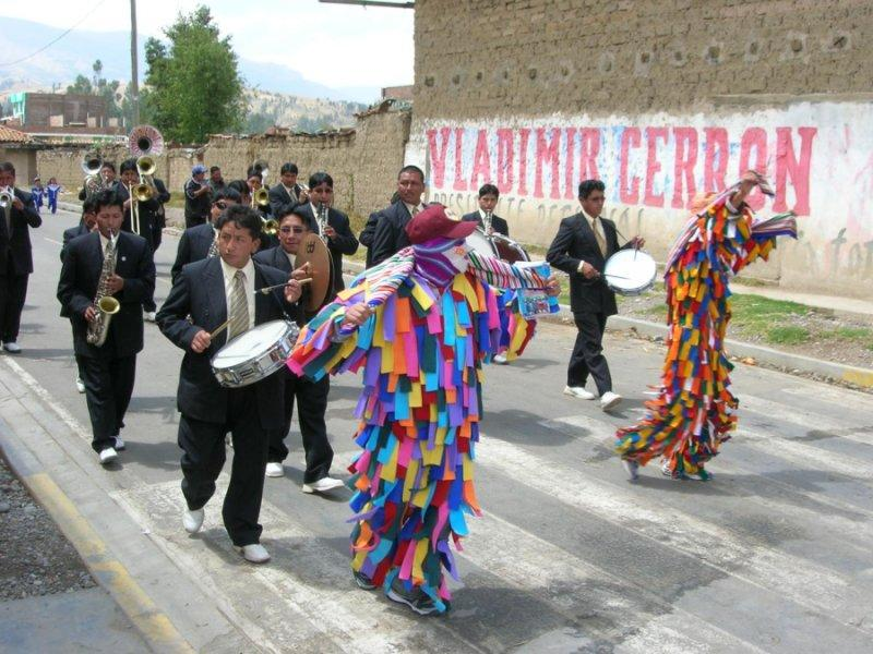 In this image, a brass band accompanies a dance-drama troupe as they process down a street in San Agustín de Cajas, Peru, during a patron-saint fiesta.