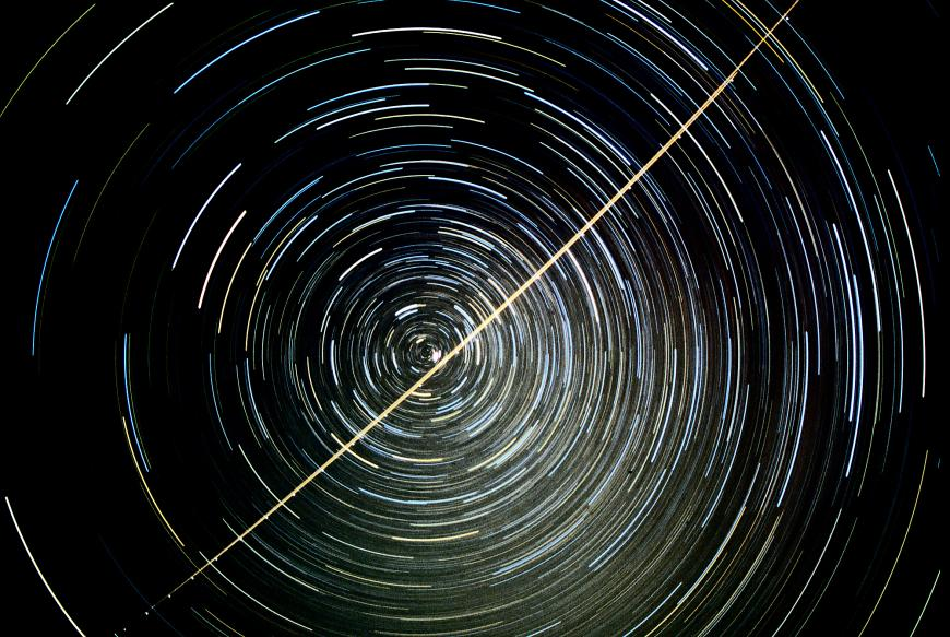 A star trail photograph showing the apparent motion of stars around the north celestial pole; Polaris is the bright star near the pole, just above the jet trail.