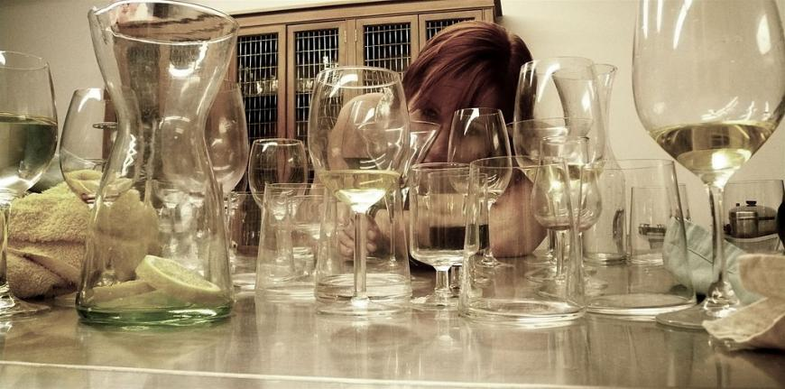 Woman staring through a group of empty glasses on a table.