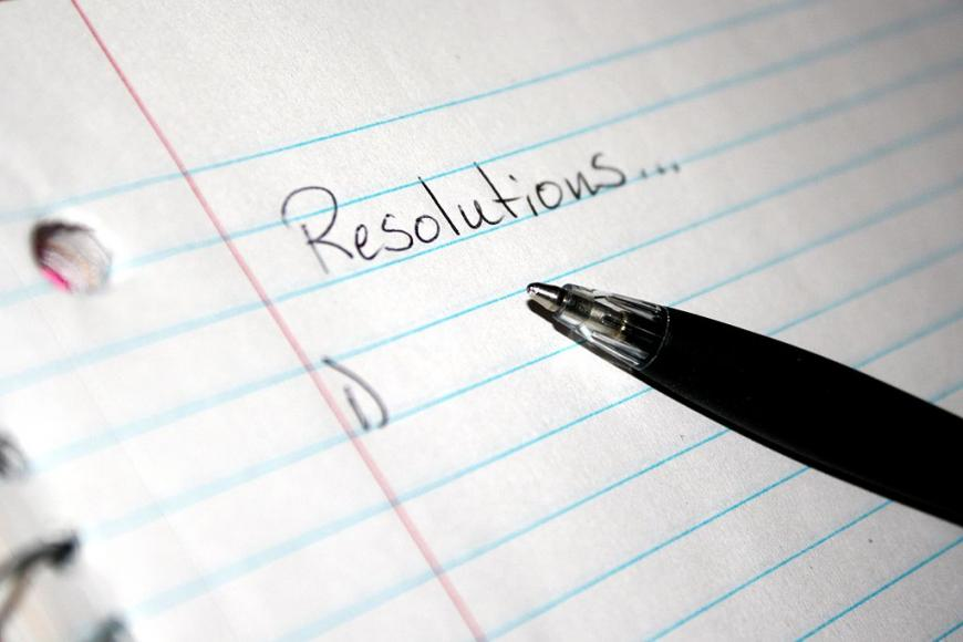 "a piece of lined paper and a pen. The word ""Resolutions"" with a listed below"