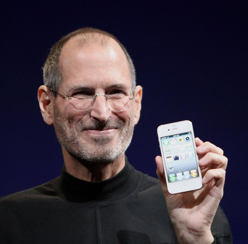 Steve Jobs, founder of Apple, holding up an iPhone
