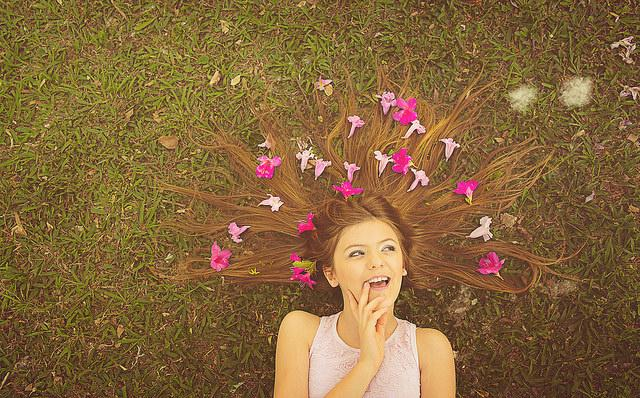 Daydreaming girl lying down with flowers in her hair.