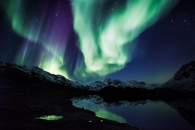 Northern lights over mountains and calm lake. CREDIT: EHRENBERG Kommunikation / Flickr (CC BY 2.0)