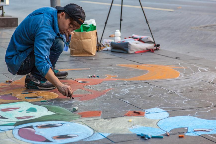 A street artist draws pokemon in chalk