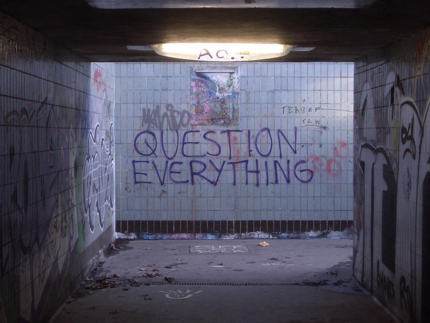 "Graffiti in a subway entrance reads ""Question Everything"""