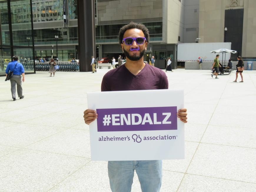Man holds sign supporting Alzheimer's research