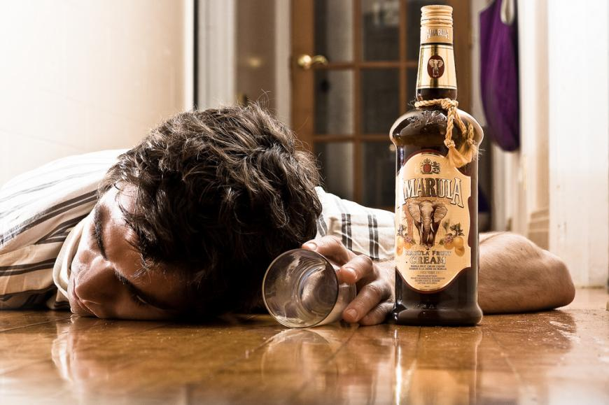 Man passed out drunk on the floor with a bottle of Amarula