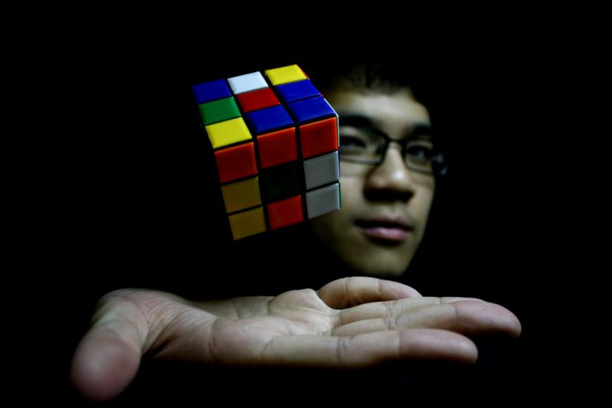 Telekinesis. Rubik's cube levitating above man's hand