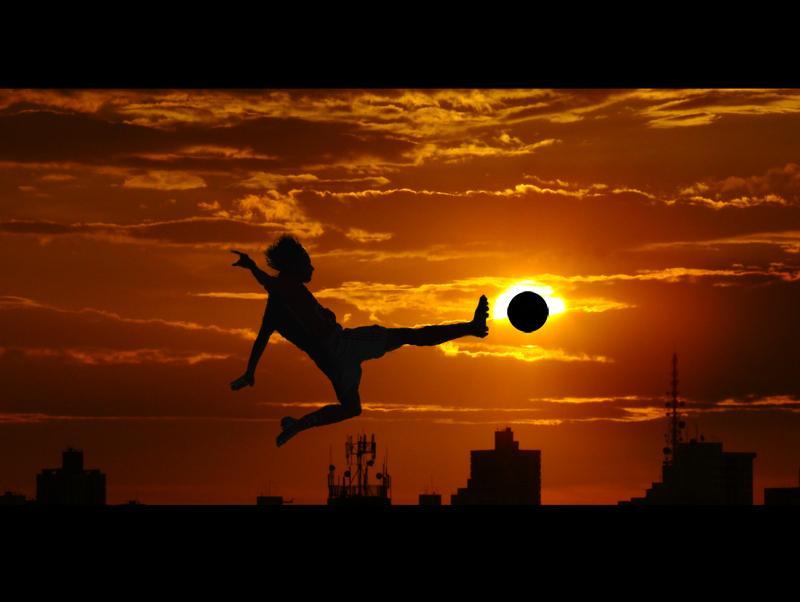 Football (soccer) silhouette against sunset.