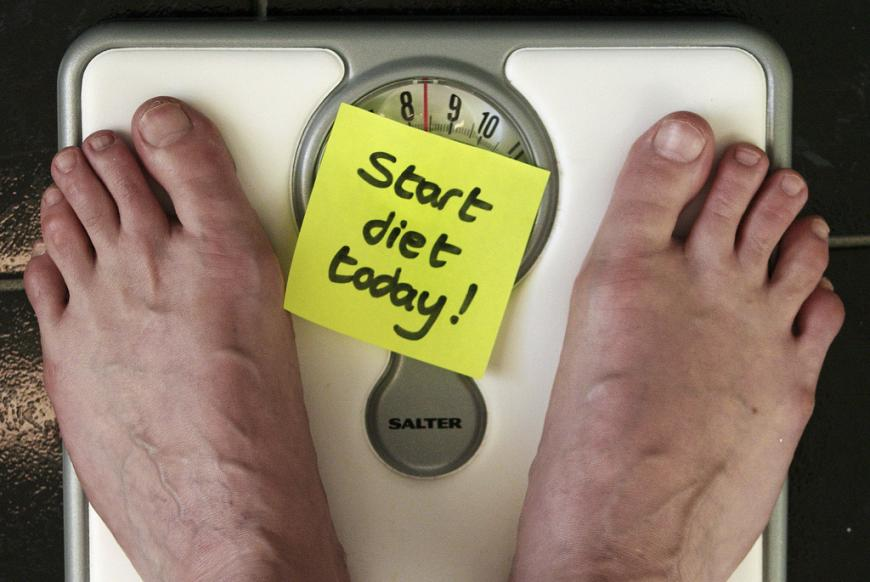 "Close up of bare feet on a weigh scale with a sticky note in between reading ""Start Diet Today"""