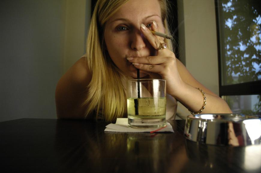 Woman smoking and drinking an alcoholic beverage