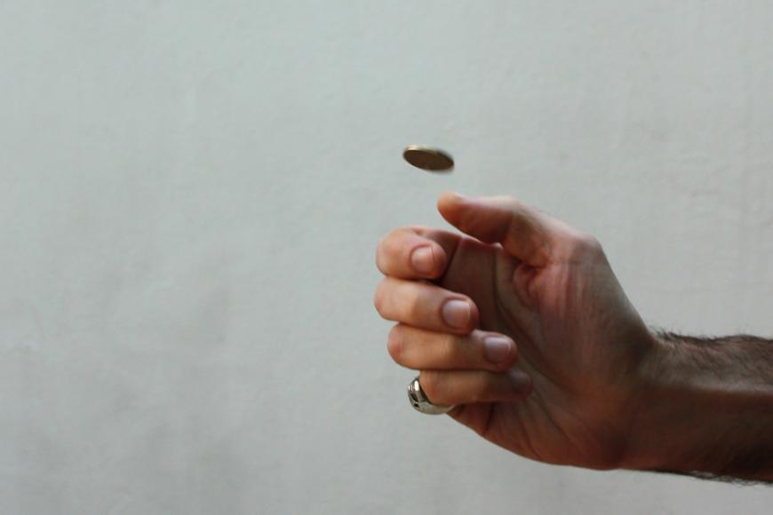 A hand flipping a coin into the air