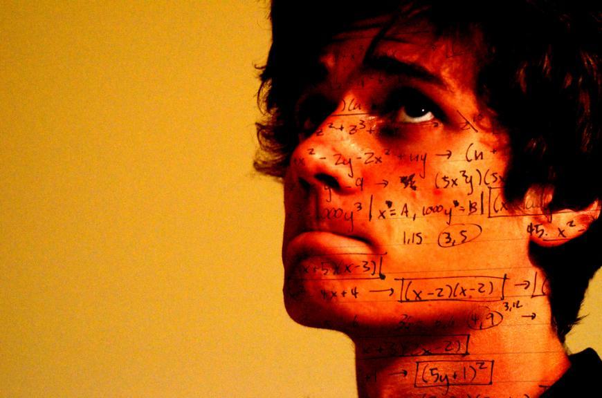 Orange image, man's face with math formulas across his skin