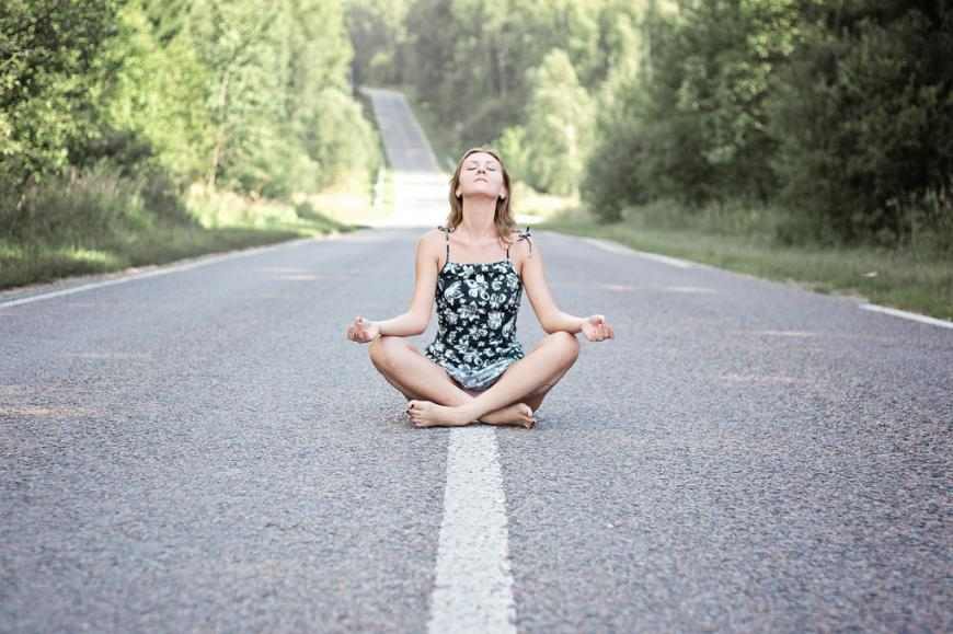 Woman meditating on a road