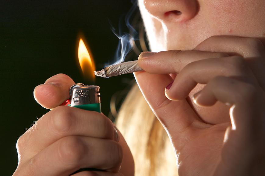 young woman smoking pot or marijuana. Lighter