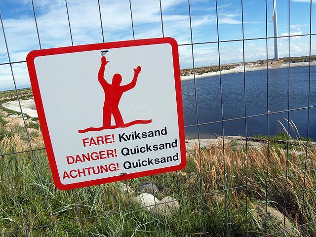 Sign on beach warning of quicksand