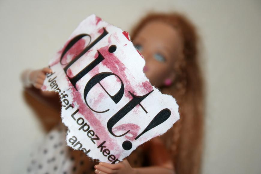 """Barbie holding a sign reading """"Diet!"""""""