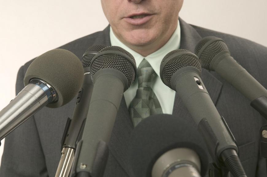 Man speaking into journalists' microphones