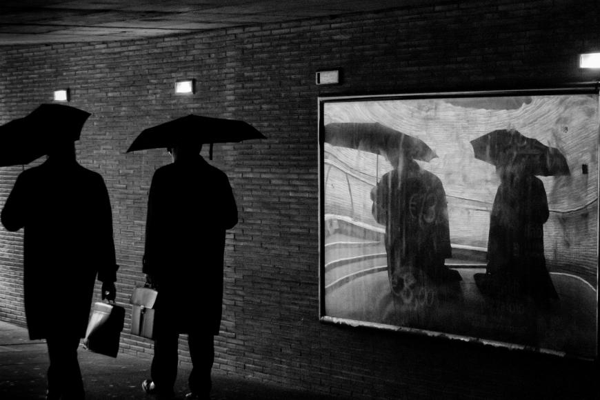 Black and white photo. Two men with umbrellas walk past a mirror