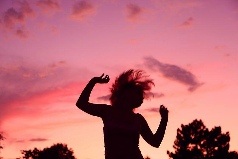 Silhouette of a dancing woman against a sunset