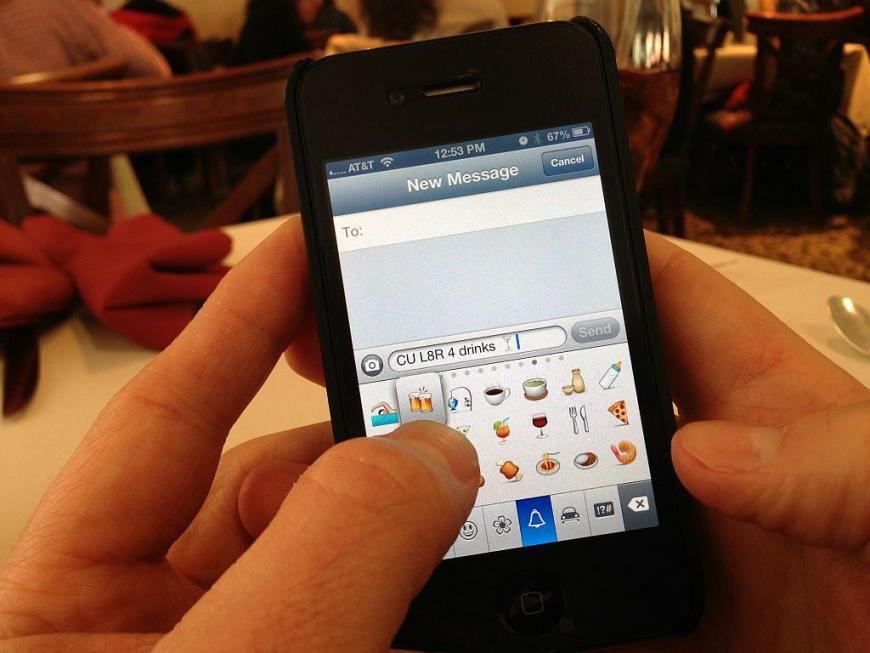 Texting on a smartphone with emojis.