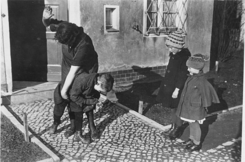 black and white photo of a father spanking his children