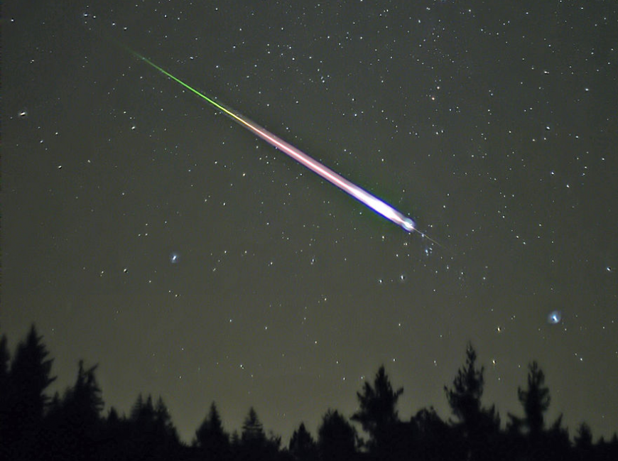 A meteor falls above the treeline