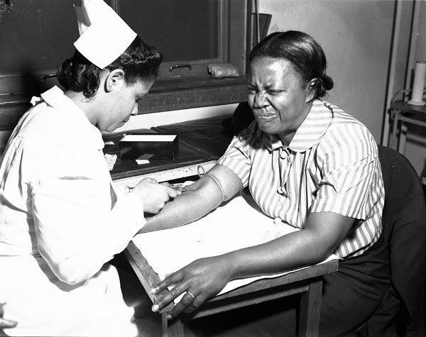 Nurse injects a woman's arm