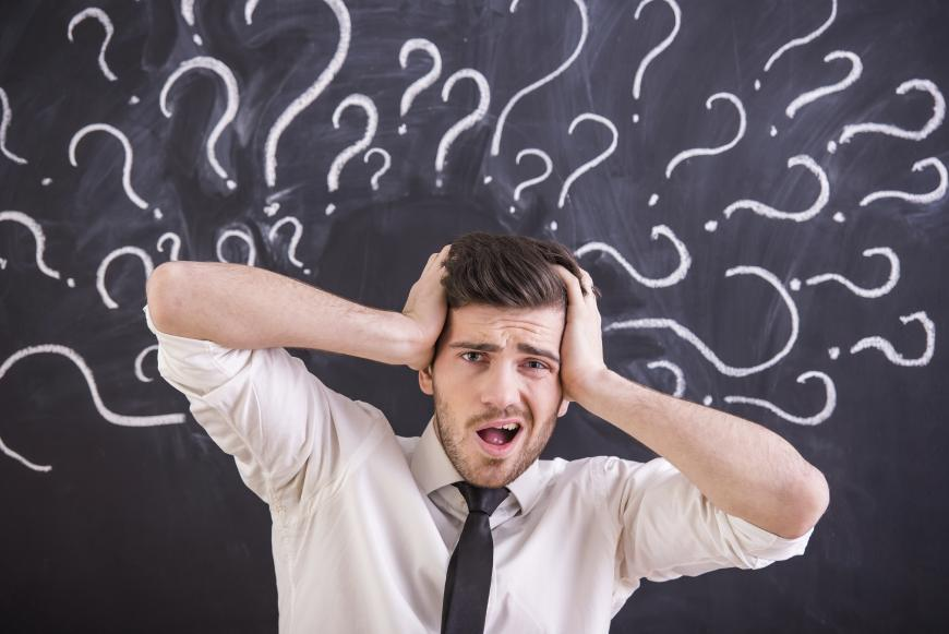 A man panicking with question marks around his head