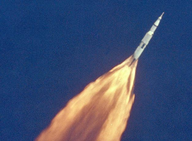 Apollo 11 Launch. A white rocketship against a dark blue sky with orange flames gushing from behind it.