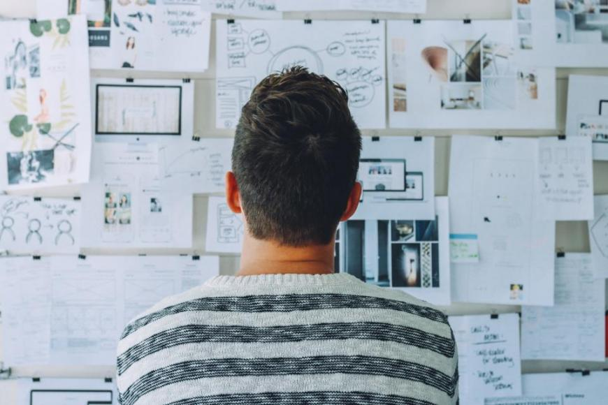 Man brainstorming, looking at an idea board