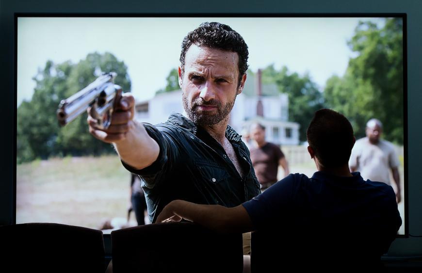 Man watching The Walking Dead in a cinema. Scenes of gun violence