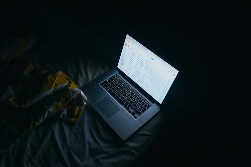 Laptop open on top of a bed
