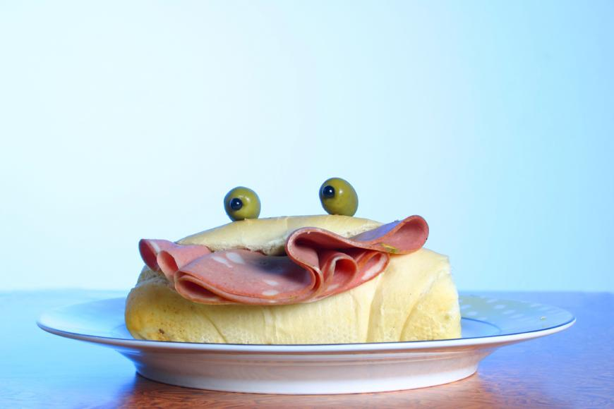 A sandwich with a mortadela smile and olive eyes.