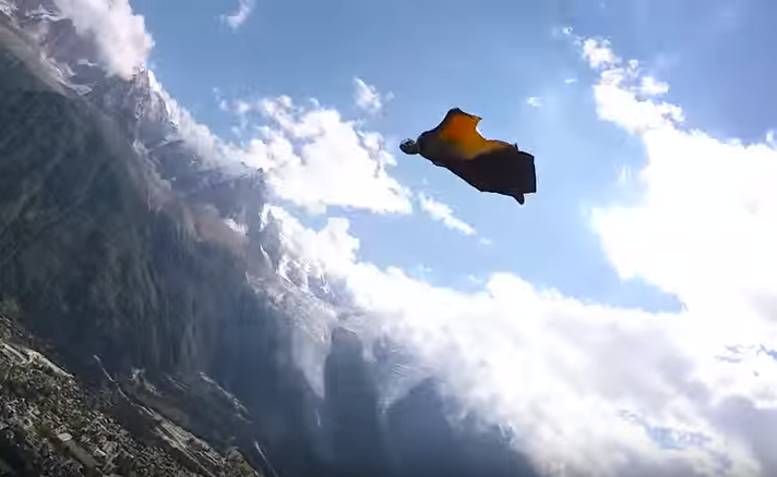 Screenshot of a wingsuit flier in the air above a small town surrounded by moutains