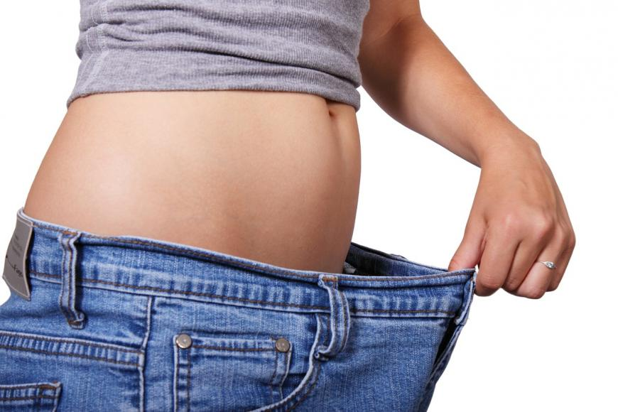 Woman holding out the pants she wore before losing weight