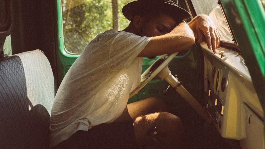 Young man sleeping over the steering wheel.