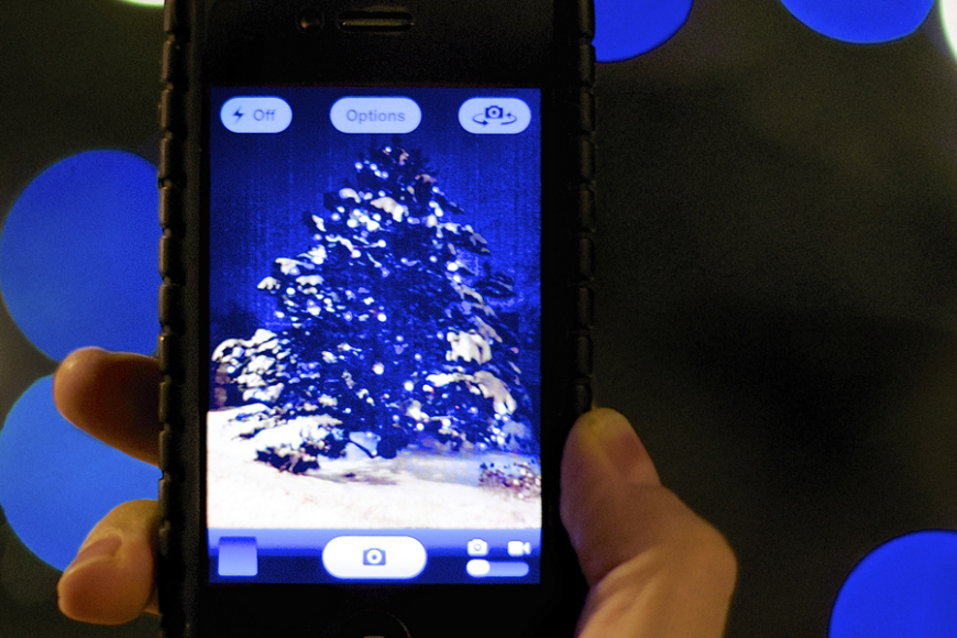 An iPhone taking a photo of a Christmas tree