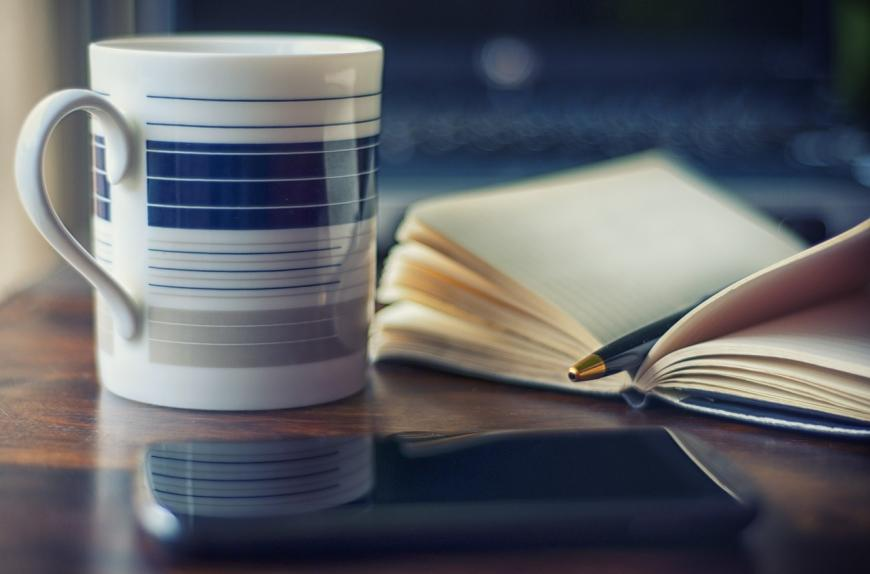 Morning coffee next to a smartphone and a day planner.