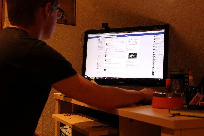 Man using Facebook on his desktop computer