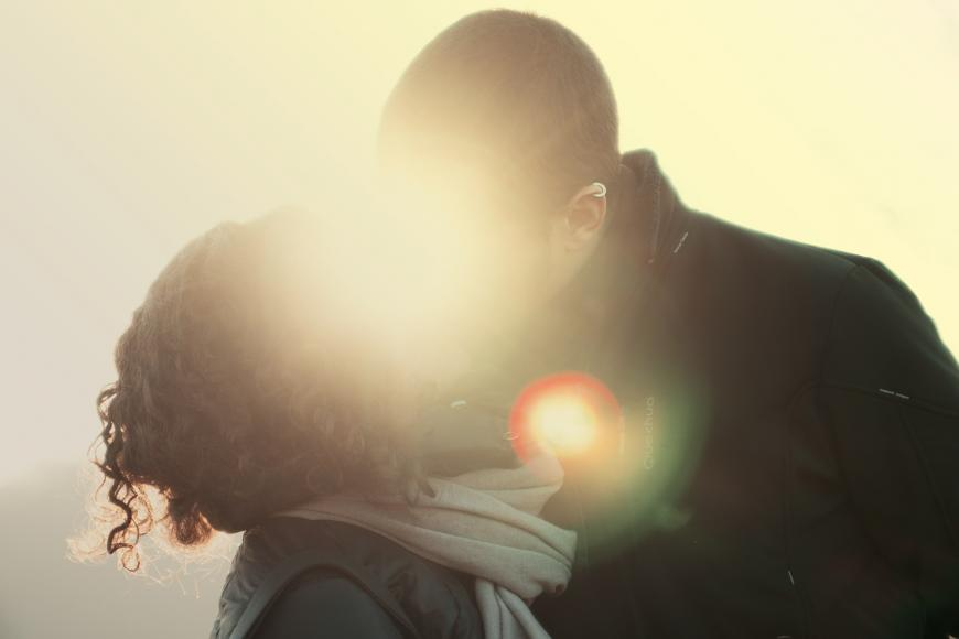 A couple kiss with a sunset directly behind them.