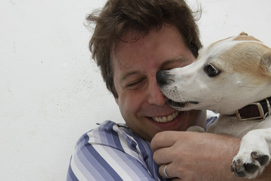 a jack russell terrier licking the nose of its owner