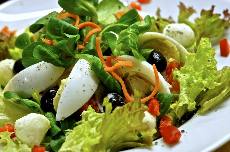 a salad with lettuce, hard boiled eggs, olives, and red bell pepper