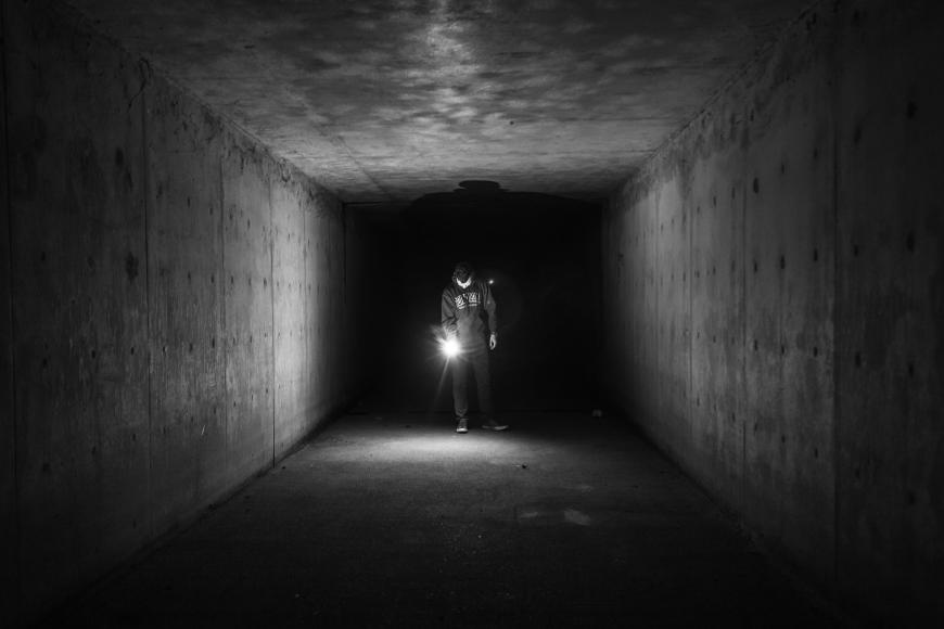 Darkness, a dark tunnel illuminated by a flashlight