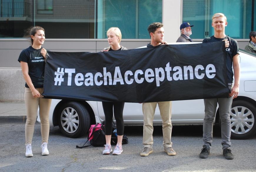 "Protests hold a banner reading ""#TeachAcceptance"""