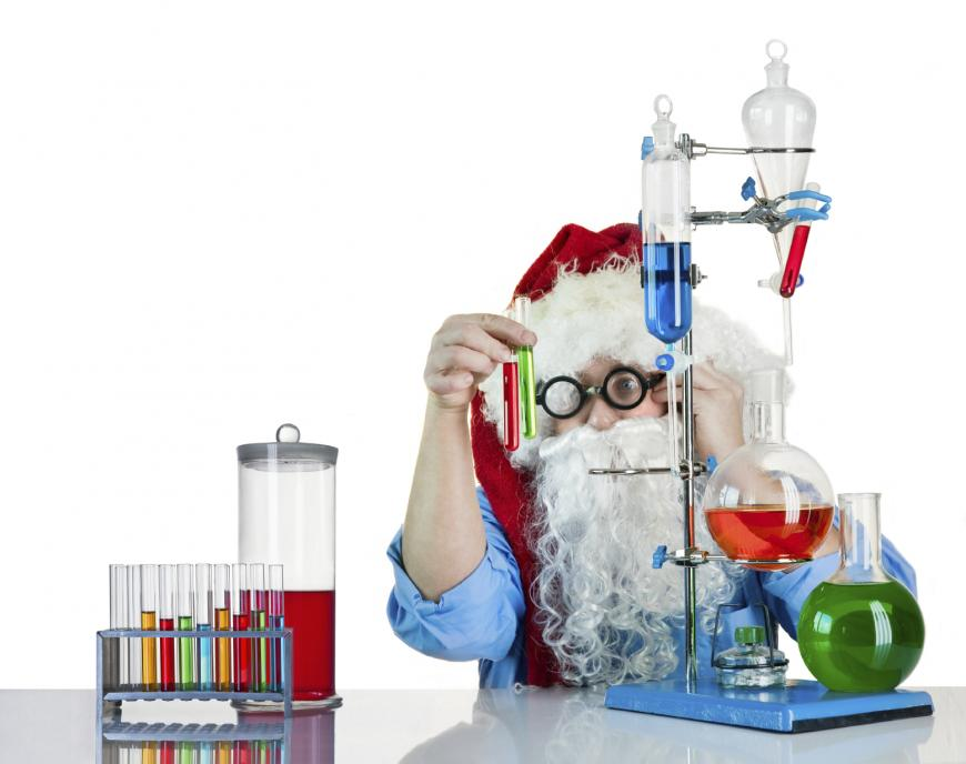 Young person dressed as Santa plays with a chemistry set.