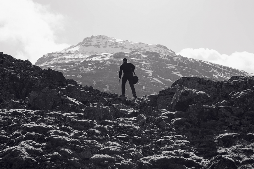 silhouette of a mountain climber standing in front of a mountain
