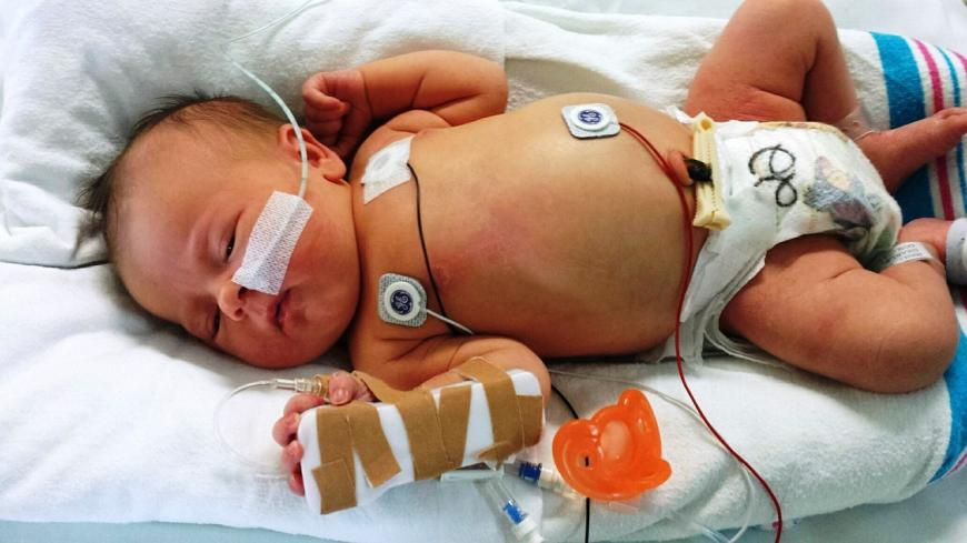Newborn infant in a hospital bed