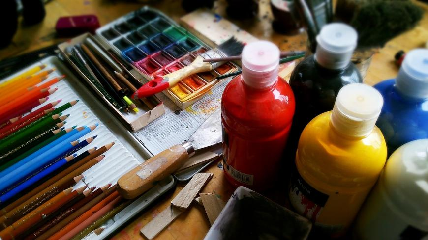Art supplies spread out on a desk: paints in bottles, colored pencils, a paintbrush, water colors, a metal scaper