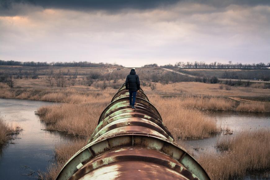 Man walking along the top of a rusty pipeline